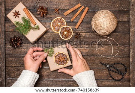 Woman decorating Christmas gifts. Presents wrapping inspirations. Hands, gift boxes, ball of jute, cinnamon sticks, anise, orange slices, fer tree branches  and scissors on rustic wooden background.  #740158639