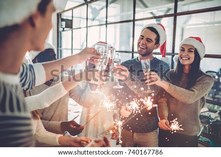Merry Christmas and Happy New Year 2018! Multiracial young creative people are celebrating holiday in modern office. Group of young business people are drinking champagne in coworking.  #740167786