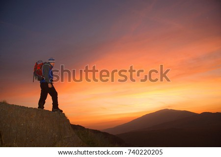 Hiker looking at the sunrise. #740220205