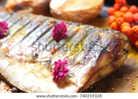 Grilled fish with cheese, honey, rowan, kalina, lemon slices, baked potatoes, pink flowers and spices on parchment paper in retro style #740259328