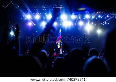 Russian flag at the concert, opposite the light from the stage #740298841