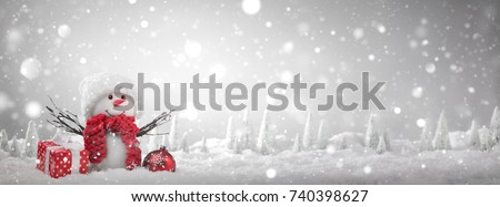 Snowman with Christmas gift on snow