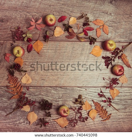 Autumn arrangement of leaves, apples and berries on a wooden background with free space for text. Top view, flat lay, copy space, season concept, toned retro effect