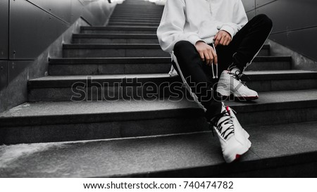 man is sitting on the stairs. Lifestyle photography. Urban wallpaper. Interior poster. Look book. Hype sneakers. Best  Royalty-Free Stock Photo #740474782