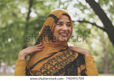 Young Muslim woman poses with scarf.  #740495704