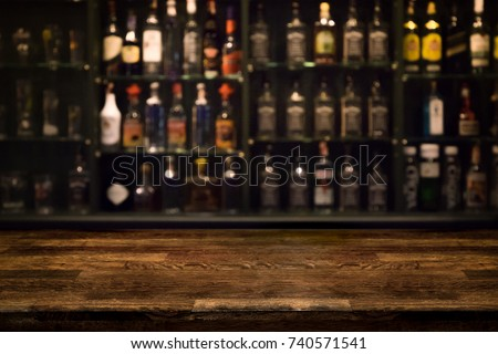 Empty wooden bar counter with defocused background and bottles of restaurant, bar or cafeteria background /for your product display Royalty-Free Stock Photo #740571541