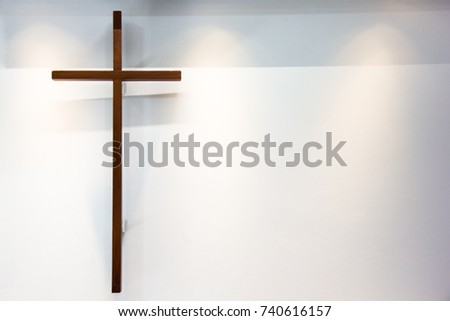 Christian wooden cross on the white and grey wall with the lighting.
