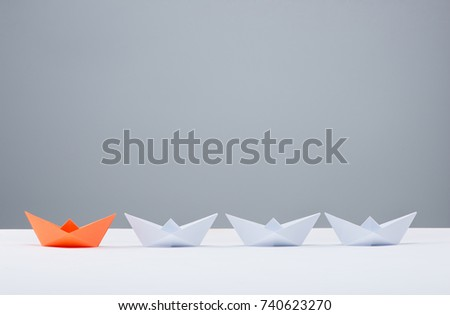 Leadership concept. Red paper ship leading among white #740623270