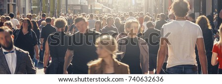 anonymous crowd of people on a shopping street Royalty-Free Stock Photo #740632636