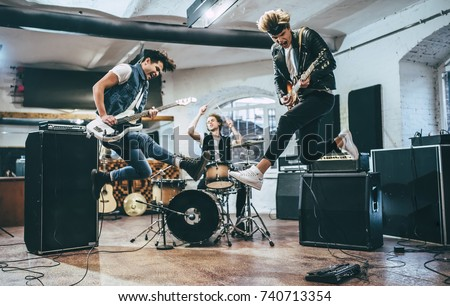 Repetition of rock music band. Bass guitar player, electric guitar player and drummer behind the drum set. Rehearsal base #740713354