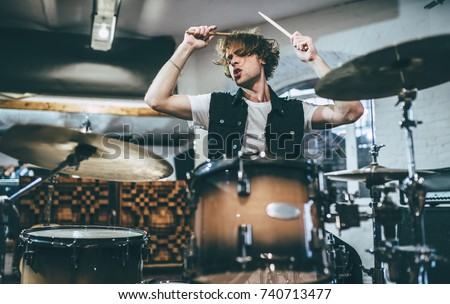 Repetition of rock music band. Drummer behind the drum set. Rehearsal base #740713477