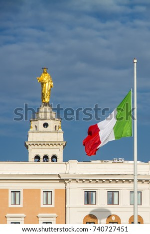 Golden statue of Jesus Christ above the Church of the Sacred Heart of Jesus at the Praetorian Barracks and the flag of Italy against the dramatic blue sky background, Rome, Italy