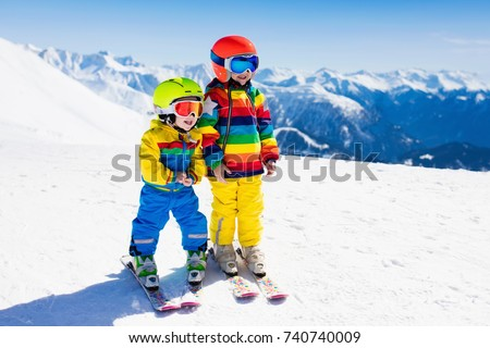 Child skiing in the mountains. Kid in ski school. Winter sport for kids. Family Christmas vacation in the Alps. Children learn downhill skiing. Alpine ski lesson for boy and girl. Outdoor snow fun. #740740009