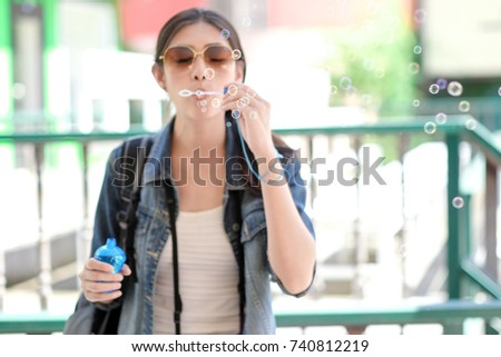Blurred image of smiling young beautiful girl in sunglasses blowing soap bubbles on summer city street. Urban life concept.Hipster girls wearing sunglass enjoying blowing soap bubbles in colorful city #740812219