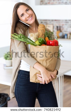 Portrait of beautiful young woman with vegetables in grocery bag at home. #740821492