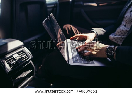 Always available. Handsome young businessman working on his laptop and talking on the phone while sitting in the car #740839651