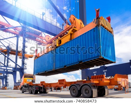 Industrial port crane lift up loading export containers box onboard from truck at port of Thailand,The port crane type's twinlift is the best solution for port operations. Royalty-Free Stock Photo #740858473