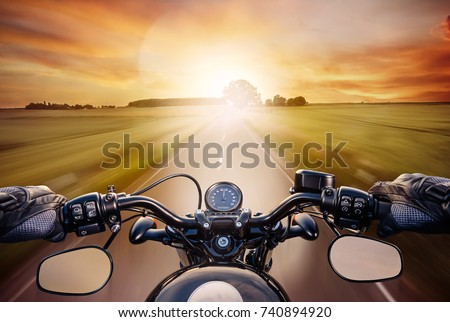 POV shot of young man riding on a motorcycle. Hands of motorcyclist on a street #740894920