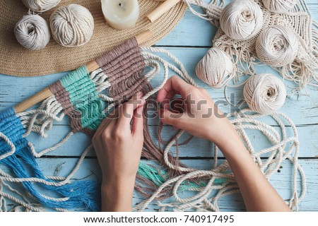 Hobby knitting macrame top view of the hand and thread on a wooden Board Royalty-Free Stock Photo #740917495