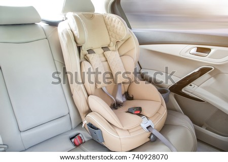 light children's car seat in a bright leather interior Royalty-Free Stock Photo #740928070
