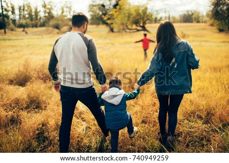 Happy family and they sons walking in autumn park and have a nice time