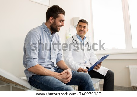 medicine, healthcare and people concept - smiling doctor with clipboard and young man patient meeting at hospital Royalty-Free Stock Photo #740979067
