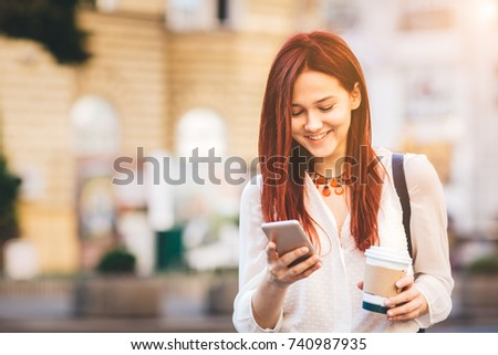 Young woman with coffee to go standing at the street and using mobile phone #740987935