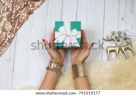 Female hands with jewelry and gift. Fashion accessories, wrist watches, glamor bracelets and rings #741019177