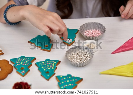 Christmas Treats. Handmade cookies, confection standing on the table. Female hands decorating gingerbreads with sweet icing beads. Christmas and New Year. #741027511