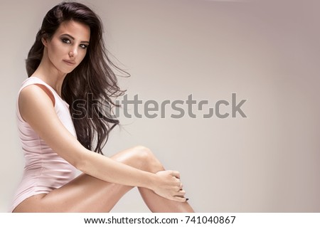 Sensual beautiful woman with long hair and perfect slim body posing in studio. #741040867