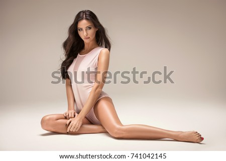 Sensual beautiful woman with long hair and perfect slim body posing in studio. #741042145