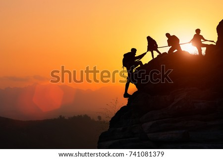 Silhouette of the climbing team helping each other while climbing up in a sunset. The concept of aid.  Royalty-Free Stock Photo #741081379