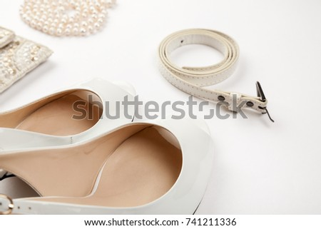 Female white shoes, bag, belt and pearl necklace on a white background #741211336