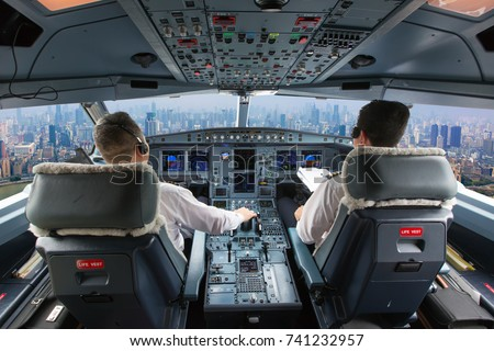 Aircraft flight deck. The pilots at work. View from airplane cockpit to the skyscrapers and city quarters. Royalty-Free Stock Photo #741232957