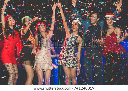 cheerful friends new year party in nightclub. Group of young people celebrate new year party throwing confetti and paper into the sky with spot light and electronic sound in night party at club. #741240019