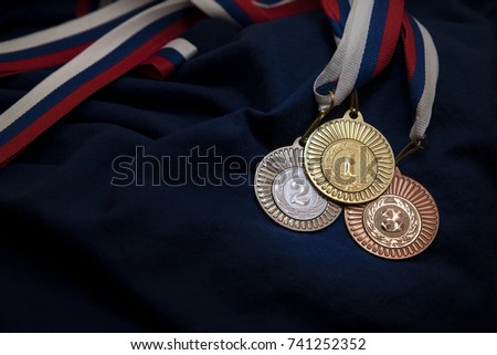Gold, silver and bronze medal with numbers One, Two and Three. Sport trophy. Blue background. Original photo for winter olympic game in pyeongchang 2018. #741252352
