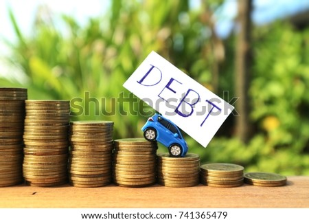 """Miniature blue car with """"Debt"""" word on white paper drives down on rolls ladder of gold coin money in blurred natural tree with blue sky and bright light  #741365479"""