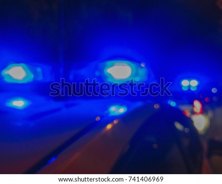 Police car lights in night time, crime scene. Night patrolling the city. Abstract blurry image. #741406969