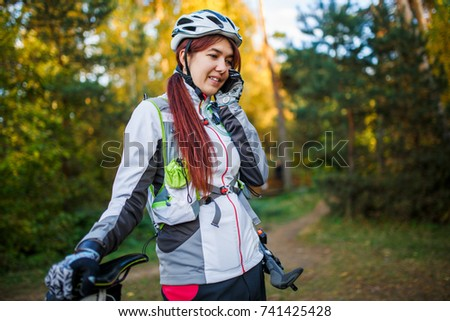 Sports girl in bicycle helmet talking on phone in autumn forest #741425428