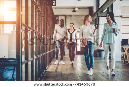 Multiracial young creative people in modern office. Group of young business people are working together. Successful hipster team in coworking. Freelancers walking in corridor. Royalty-Free Stock Photo #741463678