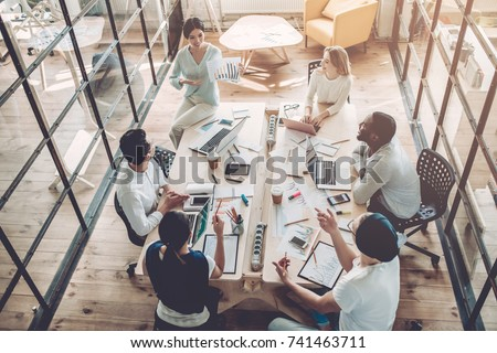 Multiracial young creative people in modern office. Group of young business people are working together with laptop, tablet, smart phone, notebook. Successful hipster team in coworking. Freelancers Royalty-Free Stock Photo #741463711