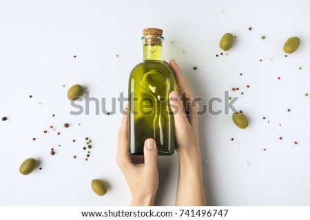 Cropped image of woman holding glass bottle of olive oil in hands isolated on white  #741496747