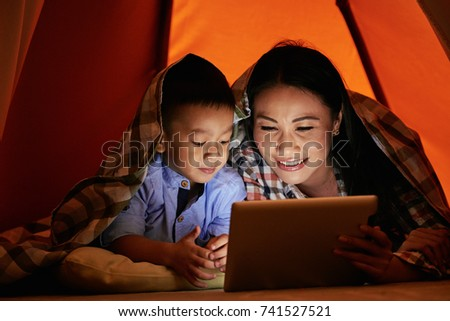 Little boy and his mother lying under blanket and playing game on digital tablet #741527521