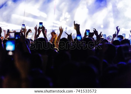 Audience recording video of band on mobile phone in concert.  #741533572