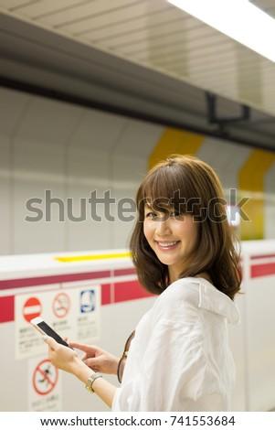 Beautiful asian woman using her smartphone. #741553684