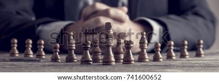 Retro style image of a businessman with clasped hands planning strategy with chess figures on an old wooden table. Royalty-Free Stock Photo #741600652