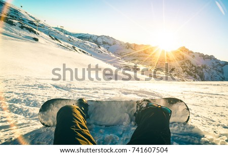 Snowboarder sitting at sunset on relax moment in french alps ski resort - Winter sport concept with adventure guy on top of mountain ready to ride down - Legs view point with teal and orange filter #741607504