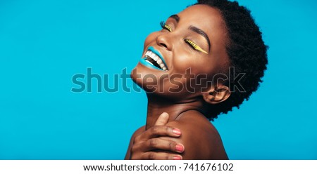 Close up of cheerful young woman with colorful makeup. Beauty portrait of female model with vivid makeup laughing on blue background. Royalty-Free Stock Photo #741676102