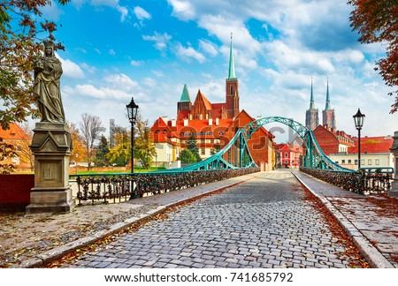 Cathedral Island in Wroclaw Poland green bridge with view on of St John the Baptist picturesque panorama medieval town blue sky and white cloud. #741685792