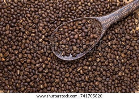 Flay lay style, Medium dark Roasted peaberry coffee beans in wooden big spoon on bamboo handcraft background. #741705820